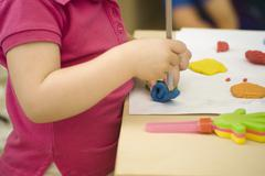 Stock Photo of Child molding clay with pencil, cropped