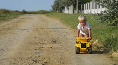 Little boy runs with big yellow car on the village roud. Stock Footage