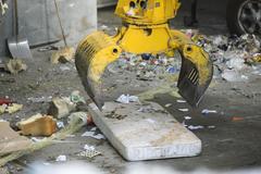 Grapple picking up mattress in garbage dump - stock photo