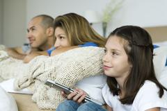 Family watching TV together, girl holding remote control Kuvituskuvat