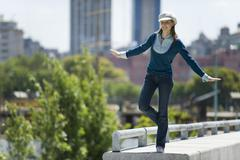 Young woman in trendy clothing standing on one leg on ledge Stock Photos