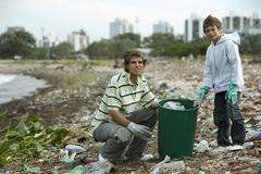 Young male and boy picking up trash on polluted shore Stock Photos