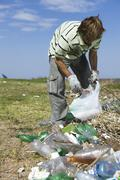 Male picking up trash in field Stock Photos