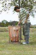 Male in park, placing trash in waste receptacle - stock photo