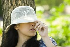 Young woman pulling sun hat over eyes Stock Photos