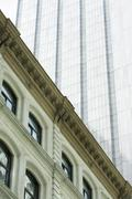 Facade of neoclassical building, modern skyscraper towering above, low angle Stock Photos