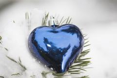Heart shaped Christmas ornament on snow-covered evergreen branch Stock Photos