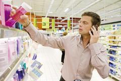 Man using cell phone, selecting bottle of shower gel from supermarket shelf Kuvituskuvat