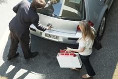 Couple opening car hatchback to stow shopping bags - stock photo