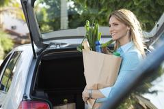Woman putting groceries in back of hatchback - stock photo
