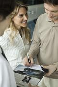 Woman watching husband as he signs document and accepts keys to new car Stock Photos