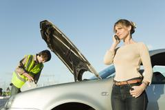 Woman making phone call while roadside assistance mechanic works to repair car - stock photo