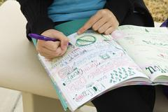 Student writing in notebook illustrated with doodles - stock photo