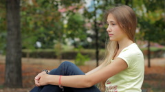 Sad And Pensive Teen Girl Sitting On Bench In Autumn City Park HD Stock Footage