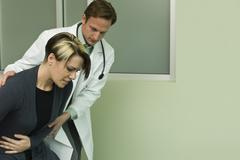 Doctor assisting patient experiencing severe abdominal pain - stock photo