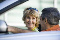 Mature couple in car together, focus on woman Stock Photos