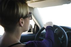 Woman driving, concentrating on road ahead Stock Photos