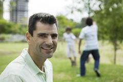 Man smiling at camera, sons playing in background Stock Photos