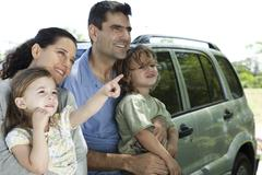 Family leaning against car, all looking as daughter points at something in - stock photo