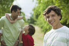Teenage boy outdoors with father and younger brothers, portrait - stock photo