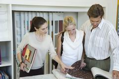 Stock Photo of Woman assisting couple choosing wallpaper samples in store