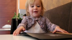 Cute two year old blond girl makes the order from the menu in a small restaurant Stock Footage