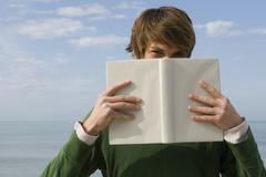 Young male holding book in front of face, portrait - stock photo