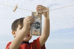 Boy hanging one million dollar bill on clothes-line - stock photo