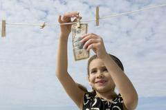 Girl hanging one million dollar bill on clothes-line - stock photo