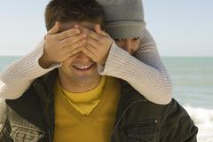 Young couple enjoying winter's day outing to beach, girl surprising boyfriend - stock photo
