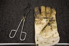 Carpet tile factory, testing lab, safety glove and crucible tongs covered in - stock photo