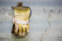 Protective work gloves held up by a binder clip on wall Stock Photos