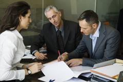 Executives signing paperwork in office Stock Photos