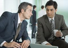 Two businessmen sitting around laptop, one with coffee cup Stock Photos