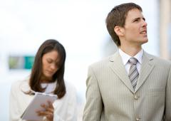 Businessman looking up while female assistant takes notes in background - stock photo