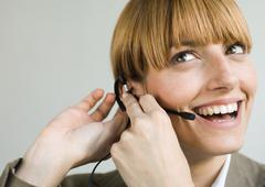 Woman smiling and putting on headset - stock photo