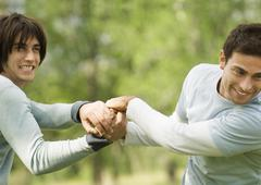 Two male friends clasping hands playfully Stock Photos
