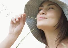 Stock Photo of Young woman with blade of grass in mouth