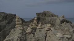 Pebbles sculptures on a rocky coast - stock footage
