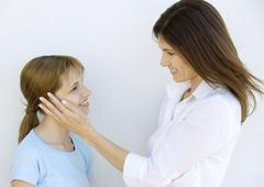 Mother looking with love at her daughter, smiling and stroking her cheek, side Stock Photos