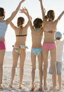 Group of kids waving on beach, rear view - stock photo