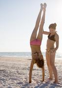 Girl helping friend do handstand on beach Stock Photos
