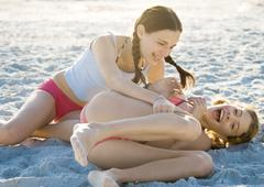 Two preteen girls on beach, one tickling the other - stock photo
