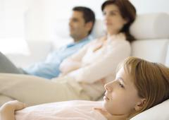 Girl reclining on sofa, parents in background Stock Photos
