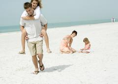 Father carrying teenage daughter piggyback on beach while mother watches Stock Photos