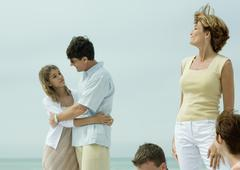 Man hugging teenage daughter while mother watches - stock photo