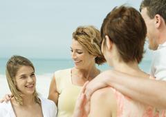 Friends talking on beach Stock Photos