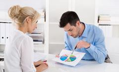 consultant explain financial success to his customer with a graphic. - stock photo