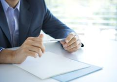 Businessman holding pen, cropped view of hands Stock Photos