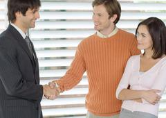 Couple concluding deal with sales executive, shaking hands Stock Photos